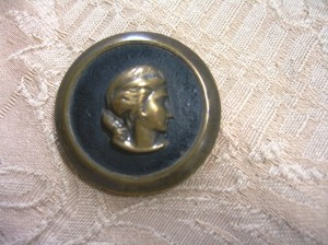 "button with brass profile on leather background 1 3/8"" diameter ©booksandbuttons"