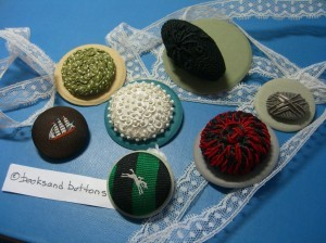"Fabric buttons: that black oblong ""trapunto"" style button is 1 3/4"" long."