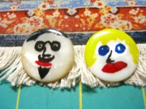 Two old mother of pearl buttons with painted faces ©booksandbuttons