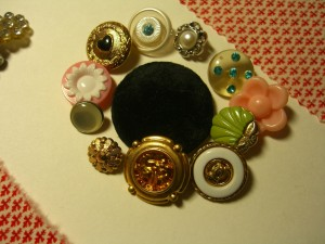 Variety of 1950 costume buttons surround a large black velvet button ©booksandbuttons